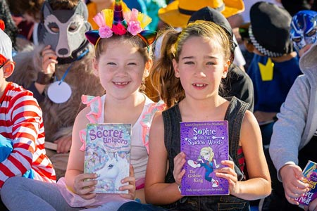 Two children in costume holding up story books