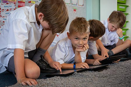 Student looking towards camera while his classmates use tablets
